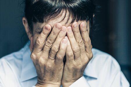 Traurige depressive, gestresste, nachdenkliche, ältere, alte Frau mittleren Alters, düster, besorgt und bedeckt ihr Gesicht Menschliche Ausdrücke, Emotionen, Gefühle und Reaktionen