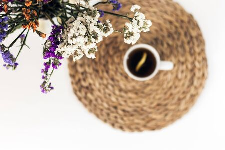 bouquet of flowers, lemon tea in a white ceramic cup on a straw wicker stand on the table, top view