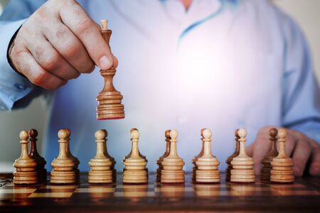 Strategy concept, hand of businessman moving wooden chess figure in play, management or leadership competition success background