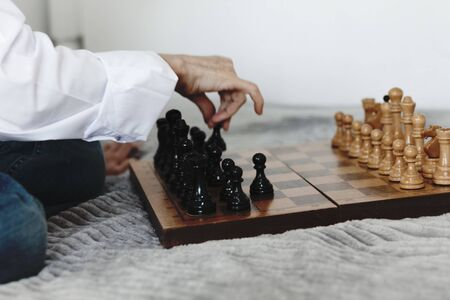 Strategy concept, hand of woman moving wooden chess figure in play, management or leadership competition business success background 免版税图像