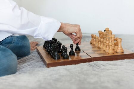 Strategy concept, hand of woman moving wooden chess figure in play, management or leadership competition business success background Фото со стока