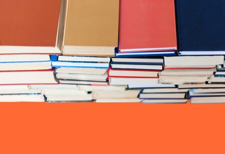 stack of book on red orange lush lava background, education concept, back to school, many books piles with copy space for text Фото со стока