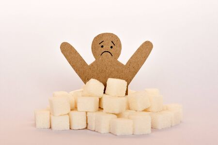 Sugar addiction, insulin resistance, unhealthy diet, figure of a cardboard man surrounded by refined sugar cubes on white background, diabetes protection medical concept