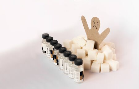 Sugar addiction, insulin resistance, unhealthy diet, figure of a cardboard man surrounded by refined sugar cubes and bottles of insulin on white background, diabetes protection medical concept