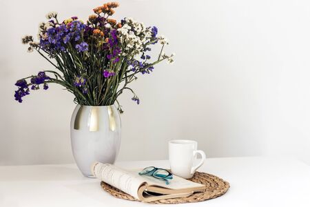 bouquet de fleurs, livre ouvert et verres, thé au citron dans une tasse en céramique blanche sur un support en osier sur la table, intérieur confortable de la maison