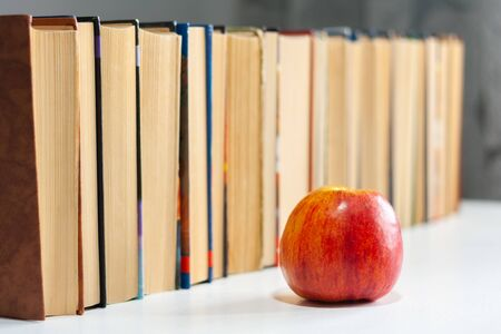 stack of hardback books on white table with red apple. Books stacking. Back to school concept. Copy Space. Education learning background Stock Photo