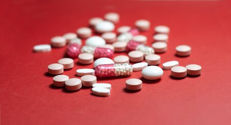 Heap of pills, tablets, capsules on red background. Drug prescription for treatment medication health care concept wth copy space