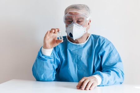 Coronavirus Covid-19 concept. Doctor in glasses and a respirator mask for protection holds a vaccine bottle. 스톡 콘텐츠