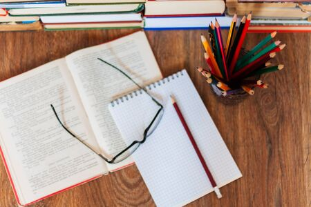 Open textbook, notebook, glasses, pencils in holder, stack of old book on wooden table, education concept background, many books piles with copy space for text Foto de archivo
