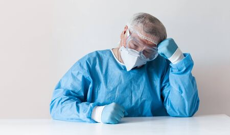 Coronavirus Covid-19 concept. Tired elderly doctor in glasses and a respirator mask for protection after hard work in hospital. 스톡 콘텐츠