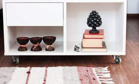 White nightstand with candles and books, next to a multi-colored rug Stockfoto