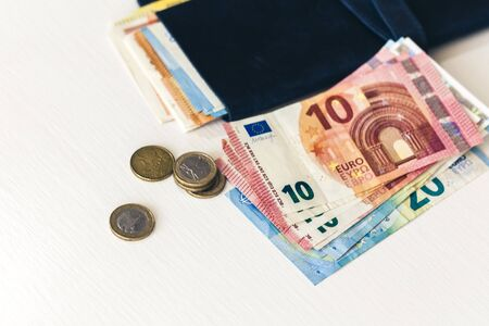 Close up money euro banknotes in blue purse and coins on white background