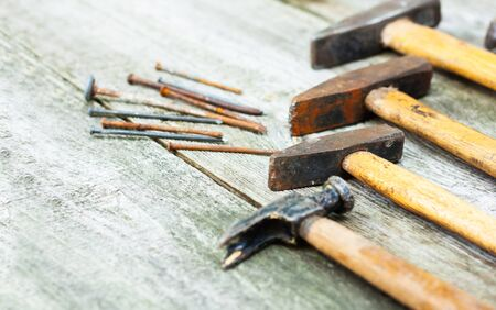 Set of vintage hand construction and carpentry tools hammers on a old wooden background, retro concept