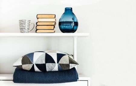 Cozy home interior decor: pillow, plaid, blue vase, stack of books, cup of coffee on a white shelf in the room. The quarantine concept of stay home, distance home education background