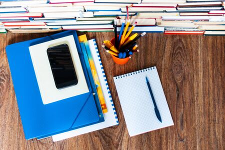 Textbook, notebook, mobile phone smartphone, stack of books. Home distance education background, stay home concept