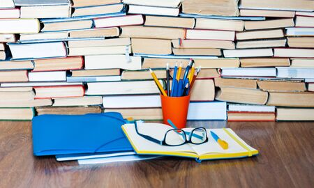 Open textbook, notebook, glasses, pencils in holder, plastic folder, stack of book. Home distance education concept background, many books piles with copy space for text Zdjęcie Seryjne