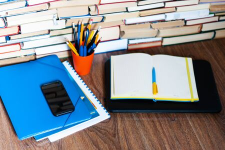 Textbook, notebook, laptop computer, mobile phone smartphone, stack of books. Home distance education background, stay home concept