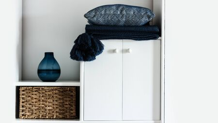 Cozy home interior decor: pillow, plaid, blue vase,  wicker box on a white shelf in the room. The quarantine concept of stay home, distance home education background