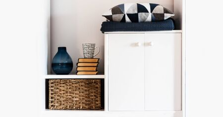 Cozy home interior decor: pillow, plaid, blue vase, stack of books, cup of coffee, wicker box on a white shelf in the room. The quarantine concept of stay home, distance home education background Foto de archivo