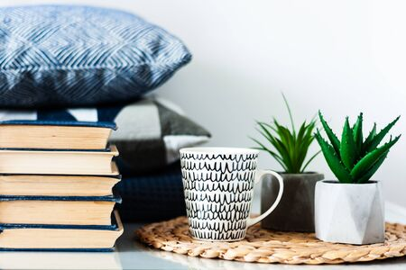 Cozy home interior decor: white and black cup, stack of books, plants in pots on a wicker stand, blue pillows on a white table in the room. Distance home education. Quarantine concept of stay home