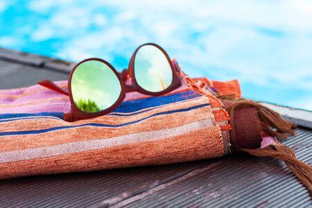 sun glasses, cover-up beachwear wrap near swimming pool, tropical background