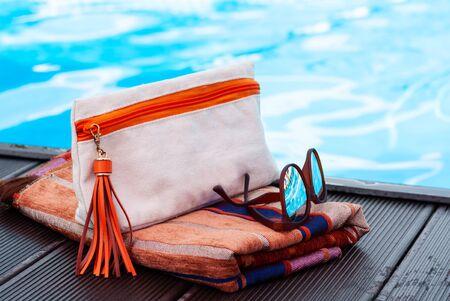 sun glasses, cosmetic bag, hat, cover-up beachwear wrap near swimming pool, tropical background