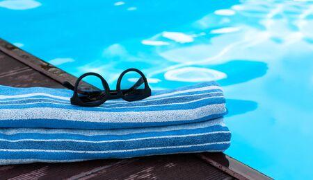 sun glasses, blue towel near swimming pool, tropical background Stok Fotoğraf