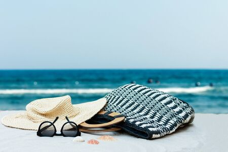 Vintage summer wicker straw beach bag, hat and sunglasses on the seashore of Catania, Sicily, Italy