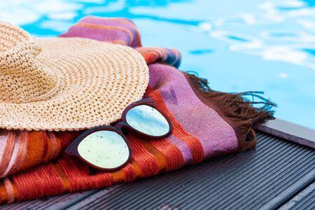 Vintage summer wicker straw beach hat, sun glasses, cover-up beachwear wrap near swimming pool, tropical background