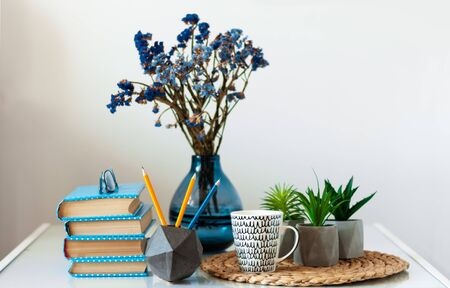 Cozy home interior decor: stack of books, plants in pots on a wicker stand, vase with flowers on a white table. Distance home education. Quarantine concept of stay home