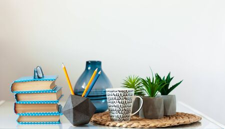Cozy home interior decor: stack of books, plants in pots on a wicker stand on a white table. Distance home education. Quarantine concept of stay home