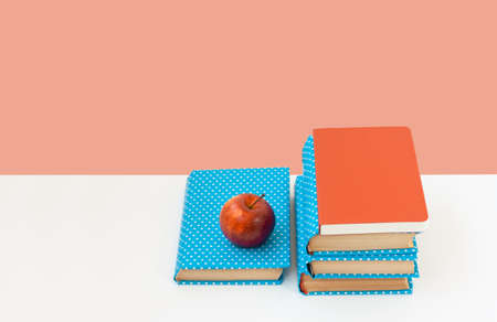 Back to school, pile of books and red apple on the white table with pink background. Distance home education. Quarantine concept of stay home