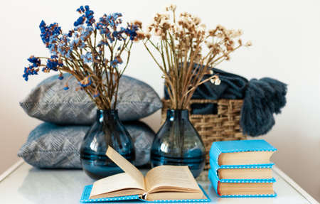 Cozy home interior decor: stack of books, vase with flowers on a white table. Distance home education. Quarantine concept of stay home Reklamní fotografie - 151147993