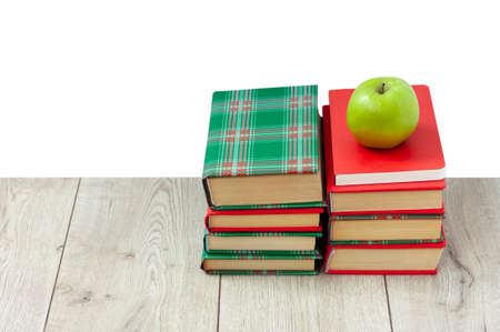 Back to school, pile of books in colorful covers and green apple on wooden table with white background. Distance home education. Quarantine concept of stay home Stock fotó