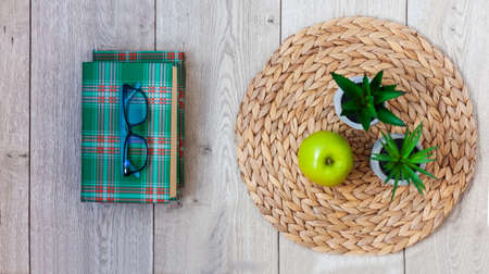 Back to school, pile of books in green covers, glasses, green apple and plants in pots on a wicker stand on wooden table. Distance home education. Quarantine concept of stay home