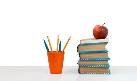 Back to school, pile of books and red apple on the white table with white background. Distance home education. Quarantine concept of stay home Stock fotó