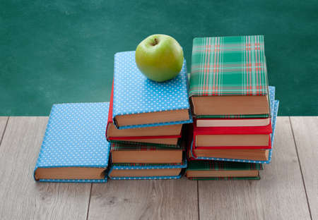 Back to school, pile of books in colorful covers and green apple on wooden table with empty green school board background. Distance home education. Quarantine concept of stay home