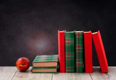 Back to school, pile of books in colorful covers and red peach on wooden table with empty black school board background. Distance home education. Quarantine concept of stay home