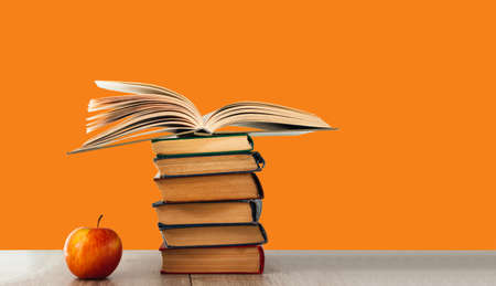 Back to school, pile of books with red apple on orange background. Distance home education. Quarantine concept of stay home Stock fotó