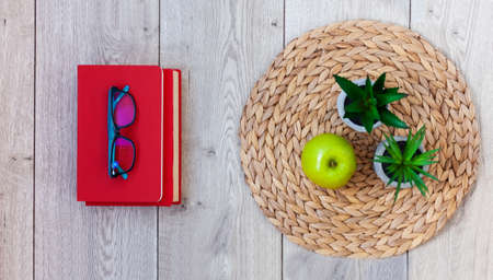 Back to school, pile of books in red covers, glasses, green apple and plants in pots on a wicker stand on wooden table. Distance home education. Quarantine concept of stay home Stock fotó