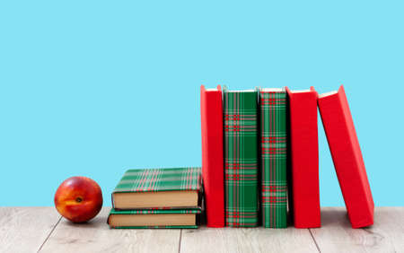 Back to school, pile of books in colorful covers and red peach on wooden table with blue background. Distance home education. Quarantine concept of stay home