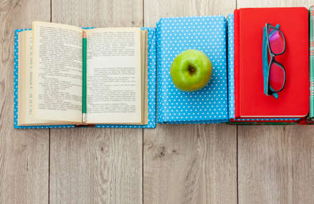 Back to school, pile of books in colorful covers, glasses and green apple on wooden table. Distance home education. Quarantine concept of stay home Stock fotó