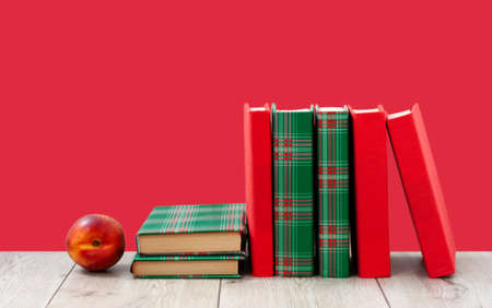 Back to school, pile of books in colorful covers and red peach on wooden table with empty pink red background. Distance home education. Quarantine concept of stay home Stock fotó
