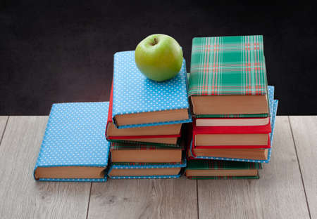 Back to school, pile of books in colorful covers and green apple on wooden table with empty black school board background. Distance home education. Quarantine concept of stay home