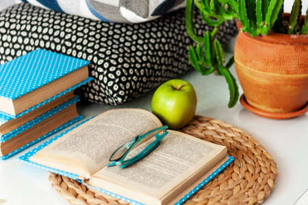 Cozy home interior decor: cup of coffee, stack of books, plants in pots, open book and green apple on a wicker stand, pillows on a white table. Distance home education.Quarantine concept of stay home