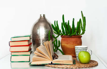 Cozy home interior decor: cup of coffee, stack of books, plants in pots, open book on a wicker stand, pillows on a white table. Distance home education.Quarantine concept of stay home.