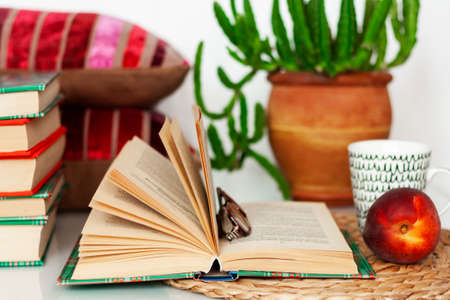 Cozy home interior decor: cup of coffee, stack of books, plants in pots, open book and red peach on a wicker stand, pillows on a white table. Distance home education.Quarantine concept of stay home Stock fotó - 152483167