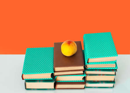 Back to school, pile of books in colorful covers and peach on wooden table with orange yellow background. Distance home education.Quarantine concept of stay home