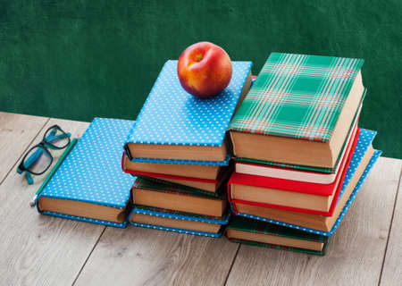 Back to school, pile of books in colorful covers and peach on wooden table with empty green school board background. Distance home education.Quarantine concept of stay home