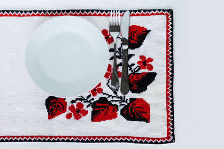 Table setting for dinner: a plate, a fork, a knife on a woven cloth napkin with an embroidered pattern, traditional handmade in Ukraine